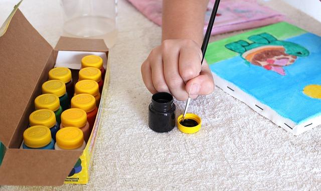 Dziecko maluje farbami.